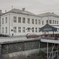Budynki i balustrada nad murowanym korytem rzeki.