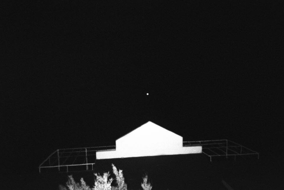 Oświetlona fasada budynku natle nocnego nieba.