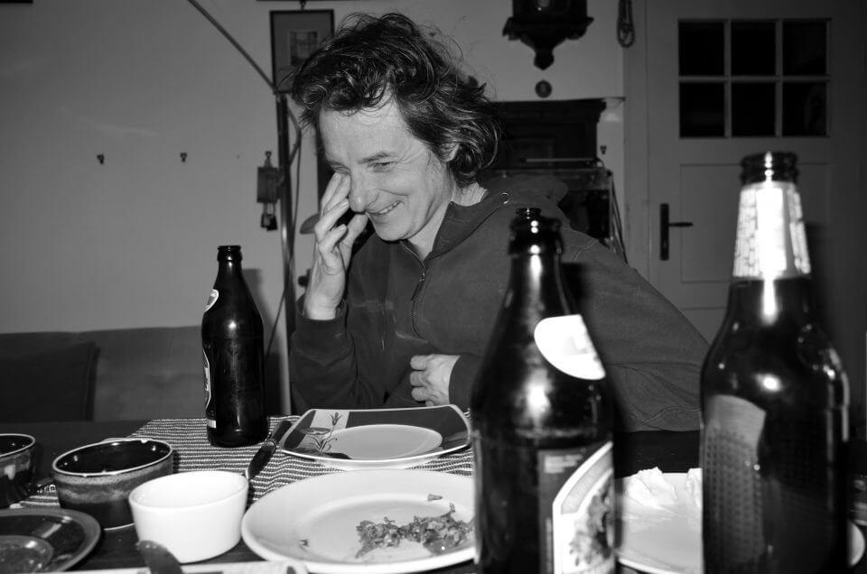 Mężczyzna siedzi przy stole zastawionym naczyniami iśmieje się.