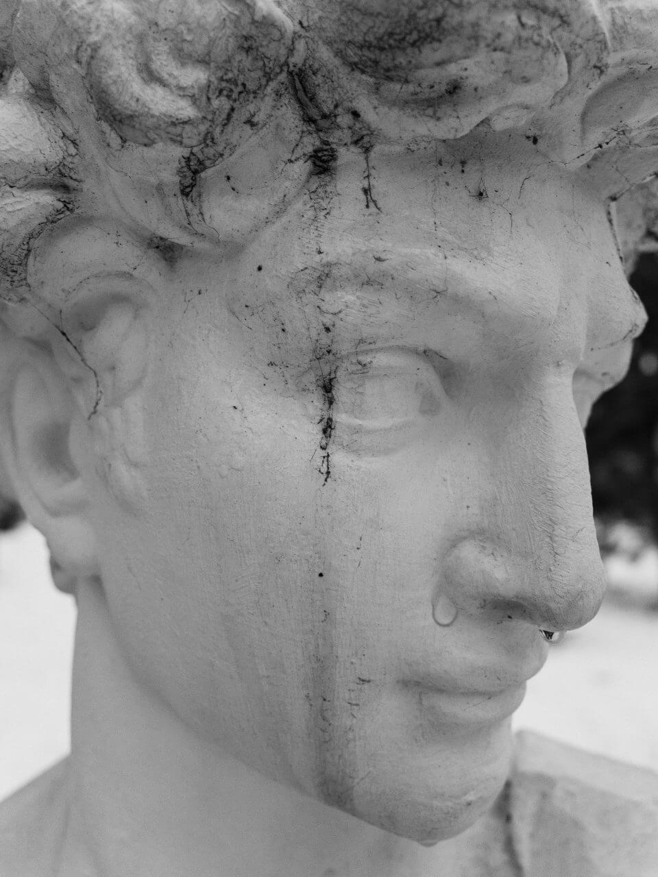 Rzeźba - twarz zmoczona deszczem.