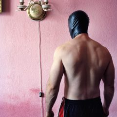 Człowiek w czarnej masce na tle różowej ściany z karniszem.