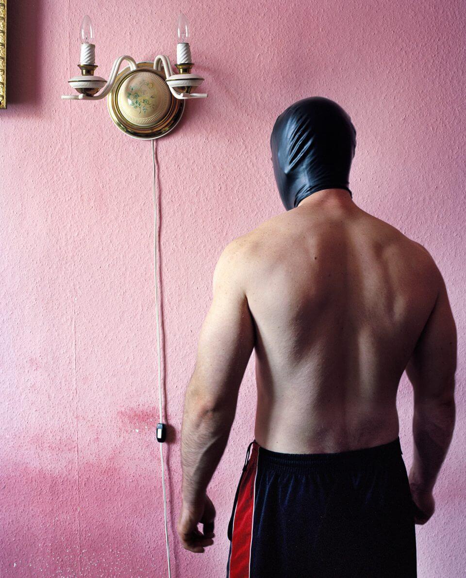 Człowiek wczarnej masce natle różowej ściany zkarniszem.