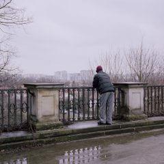 Mężczyzna stojący przy balustradzie i spoglądający na miasto w tle.