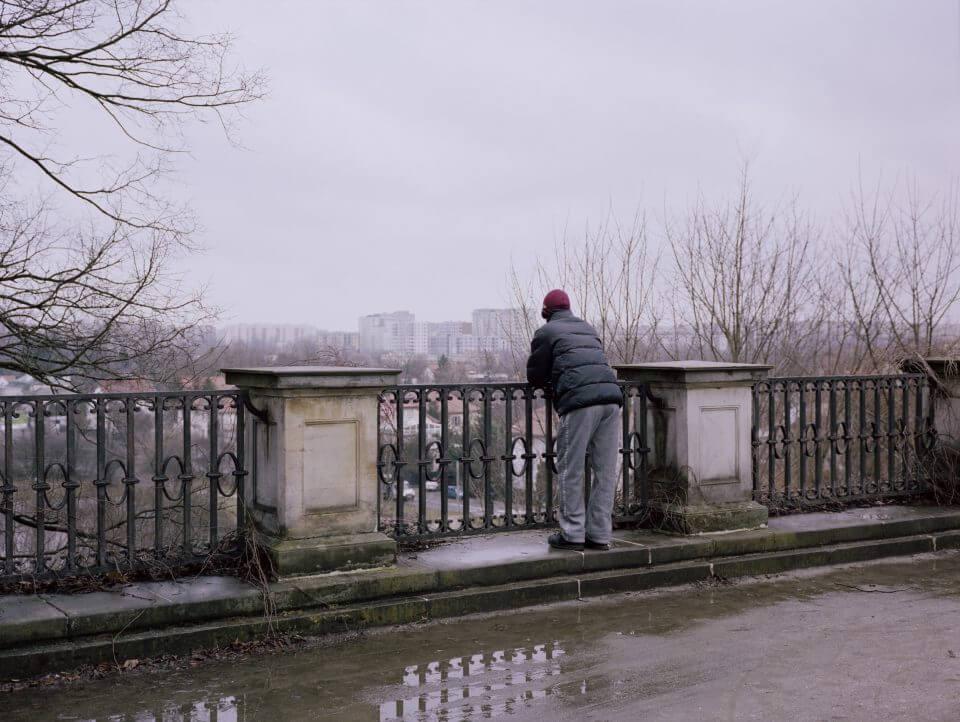 Mężczyzna stojący przy balustradzie ispoglądający namiasto wtle.