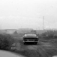 Stare auto z kominami fabryki w tle